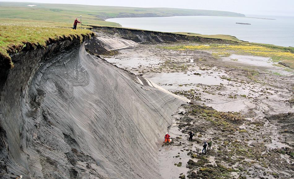 AWI-Permafrostforscherin Stefanie Weege erfasst die GPS-Koordinaten der erodierenden Steilküste auf der kanadischen Permafrost-Insel Herschel Island. Die Daten helfen der Wissenschaftlerin, das Ausmaß der Erosion zu bestimmen. Foto: Boris Radosavljevic