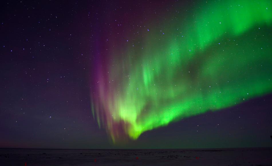Je nachdem, ob Elektronen mit Sauerstoff oder Stickstoff kollidieren, ist das resultierende Licht entweder grün oder rot, so dass die Aurora einen wirbelnden Vorhang aus verschiedenen Lichtfarben bildet.  Bild: Michael Wenger